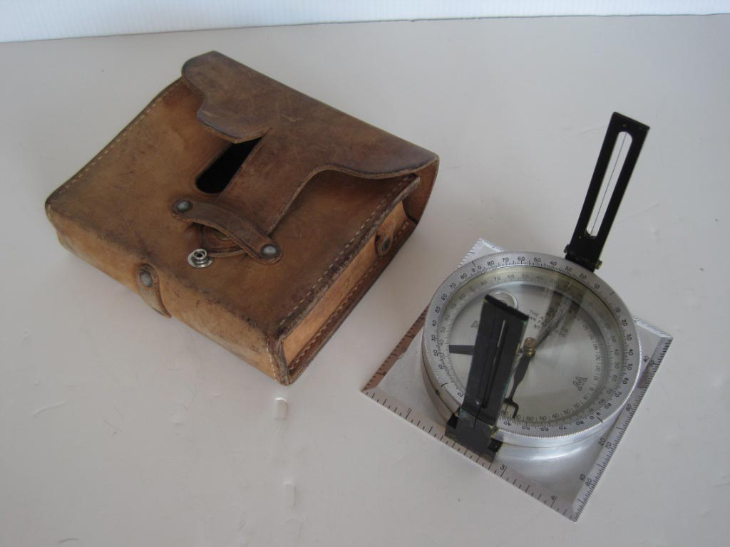 Lietz staff compass, socket and leather case, c. 1950. A staff compass was used by early foresters to locate property boundaries. There's a brass socket that fits onto the bottom of the compass to mount a staff.