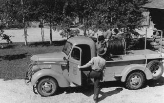 Employees ready a 3/4 ton fire truck at the Marcel Ranger Station on the Chippewa National Forest in 1940; equipped with a hose, pump and water tank. (NARA)